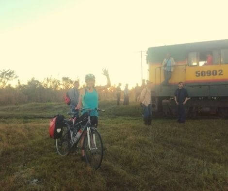 A train broke down in the middle of the road. Only cyclist can sneak past the traffic jam.