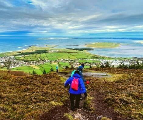 View over the coast from the top of Knocknarea with some hikers on decent - top 10 trail routes hiking and trail running in Ireland