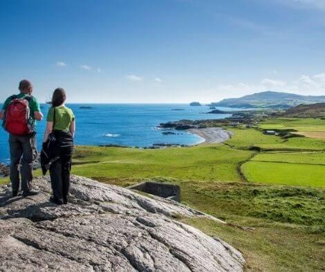 2 people standing on a rock overlooking the Irish coastline on their Irish history tour